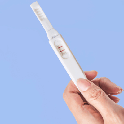hand holding a pregnancy test after getting pregnant quickly