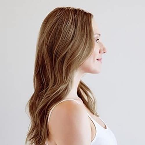 Profile view of model with long wavy hair dyed light brown