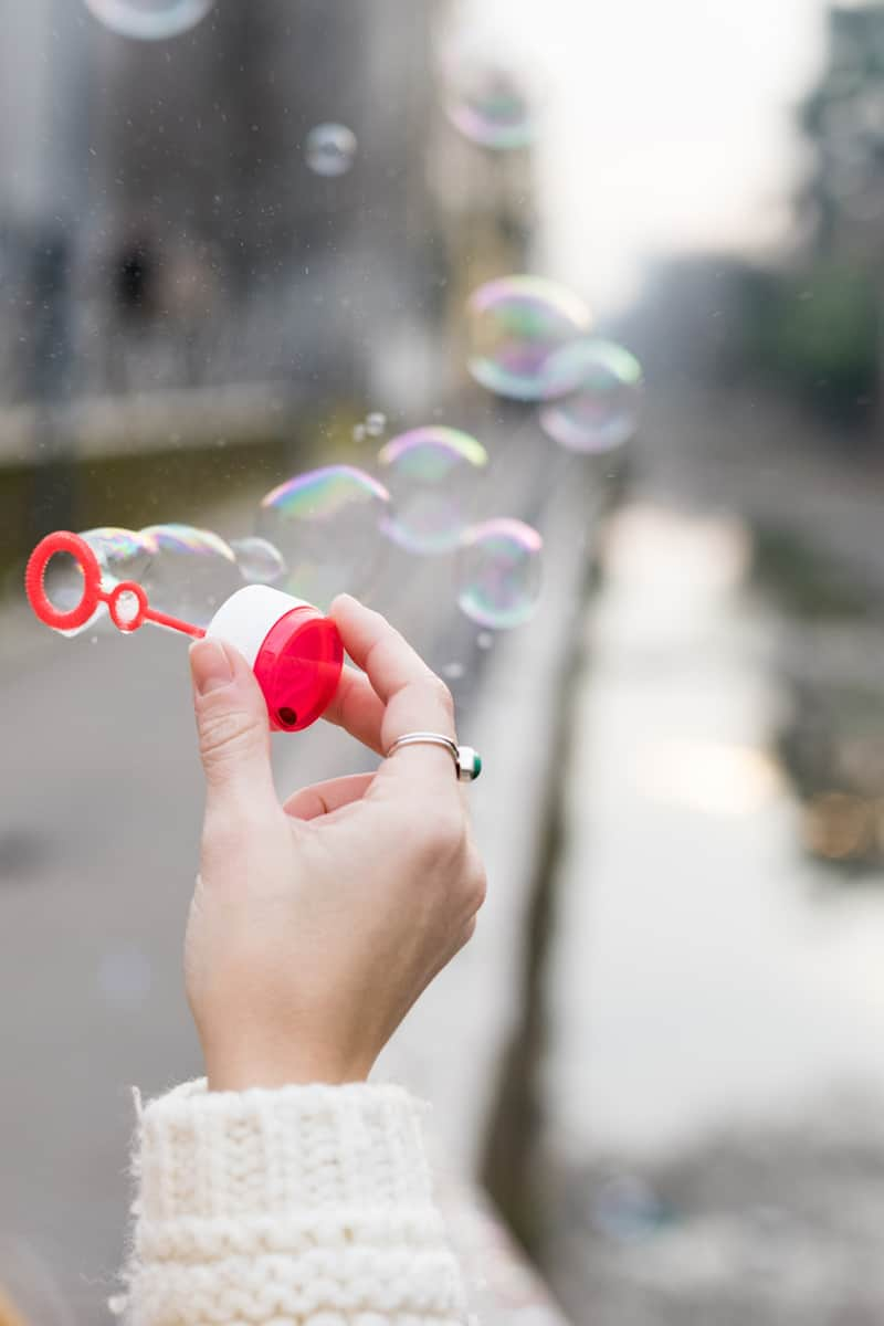 Hand holding a red bubble wand with bubbles floating through the air