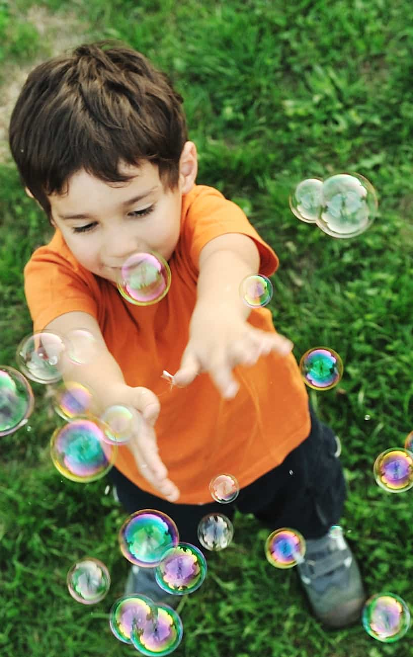 overhead view of boy in orange shirt reaching up towards bubbles floating in front of him.