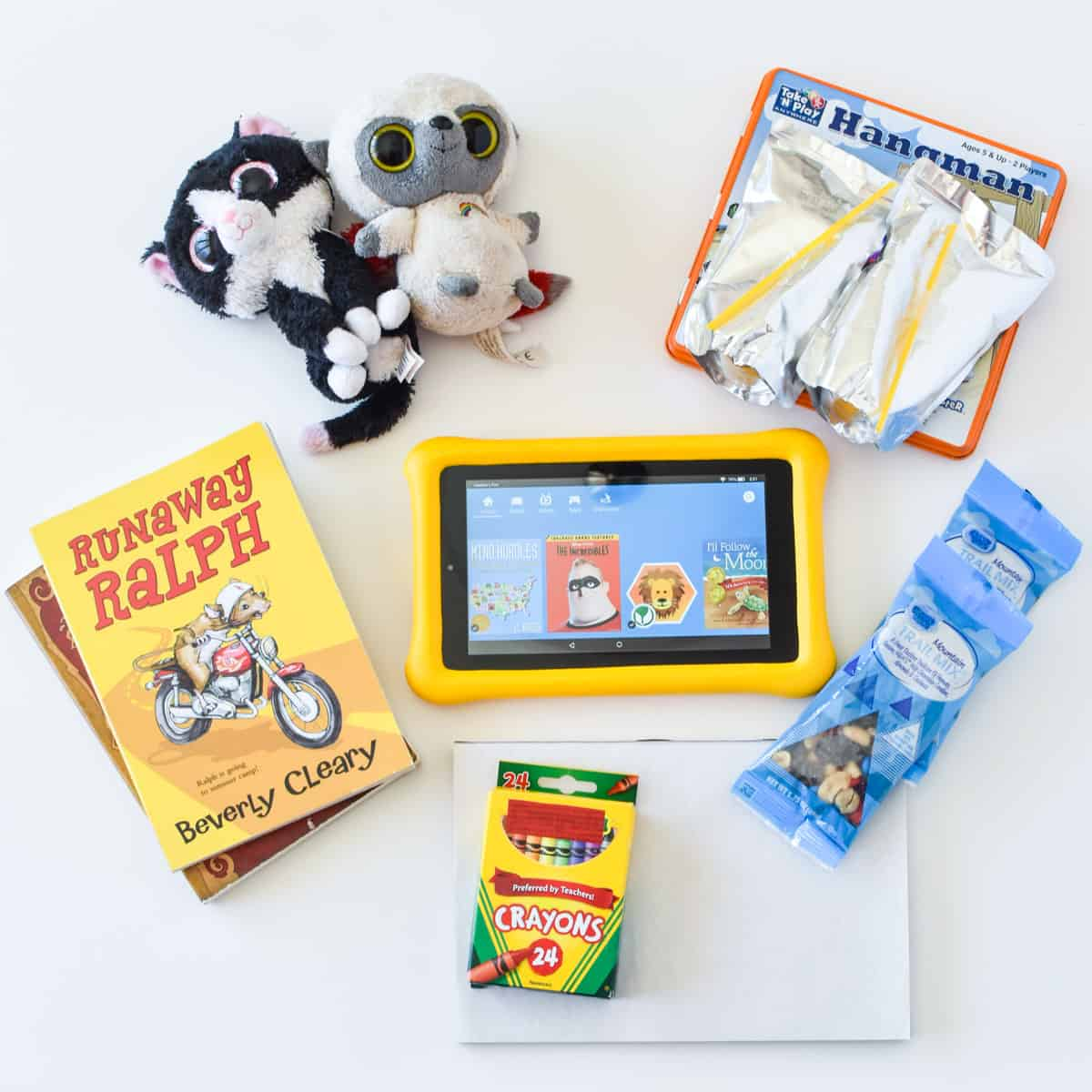 books stuffed animals, tablet, crayons and other road trip essentials for kids