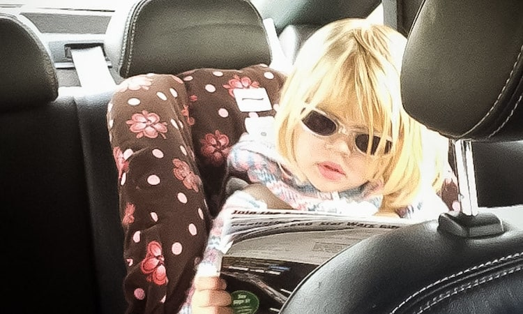 toddler girl in backseat reading a magazine on a road trip
