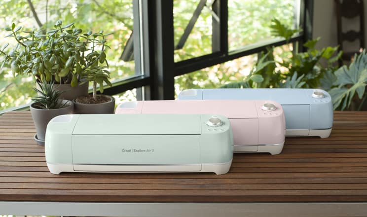 Mint green, pink and blue Cricut Explore Air 2 machines on a wood slatted table