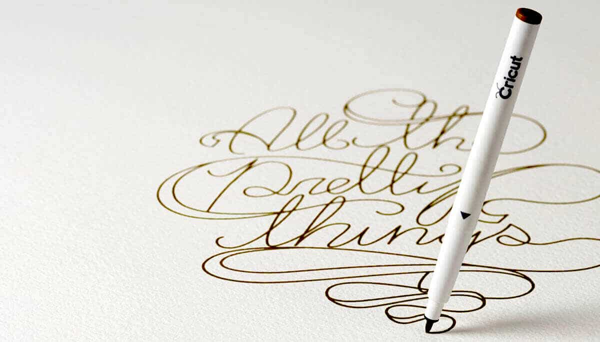 Pen writing pretty script in gold ink