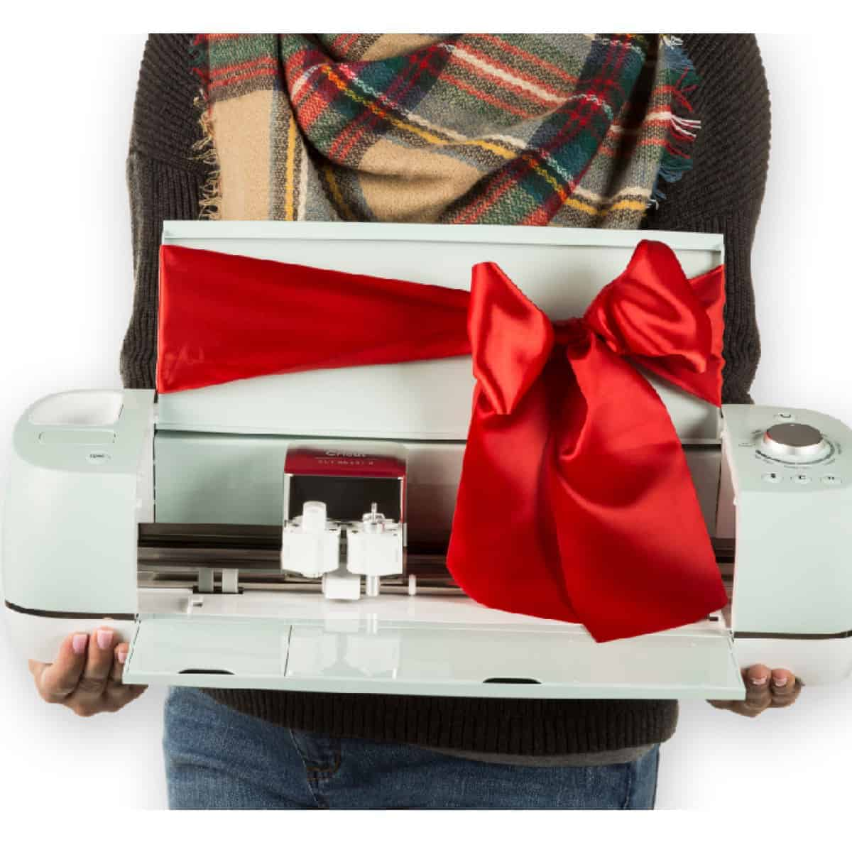 Woman in scarf holding a Mint green Cricut Explore air 2 with a red bow tied around it