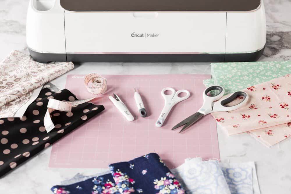 Scissrs, quill, tweezers and sewing supplies in front of a Cricut Maker