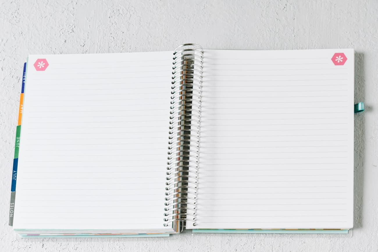 open pages of spiral bound notebook with tabs on the left side