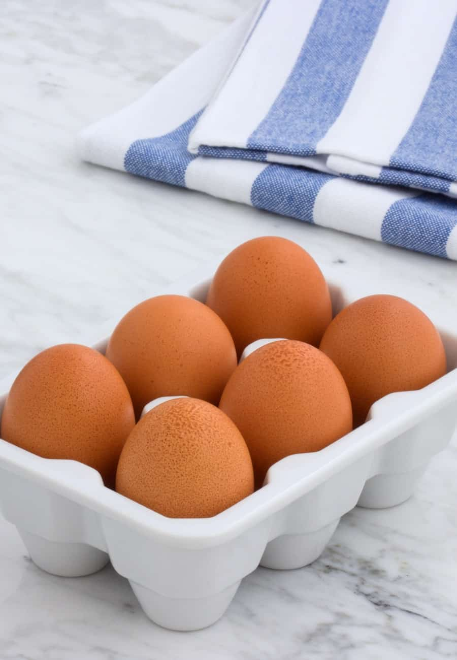 brown eggs in ceramic holder with towel