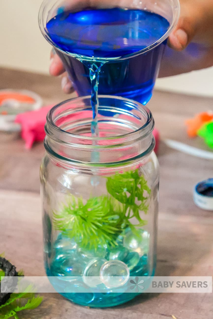 pouring blue water into homemade mason jar aquarium
