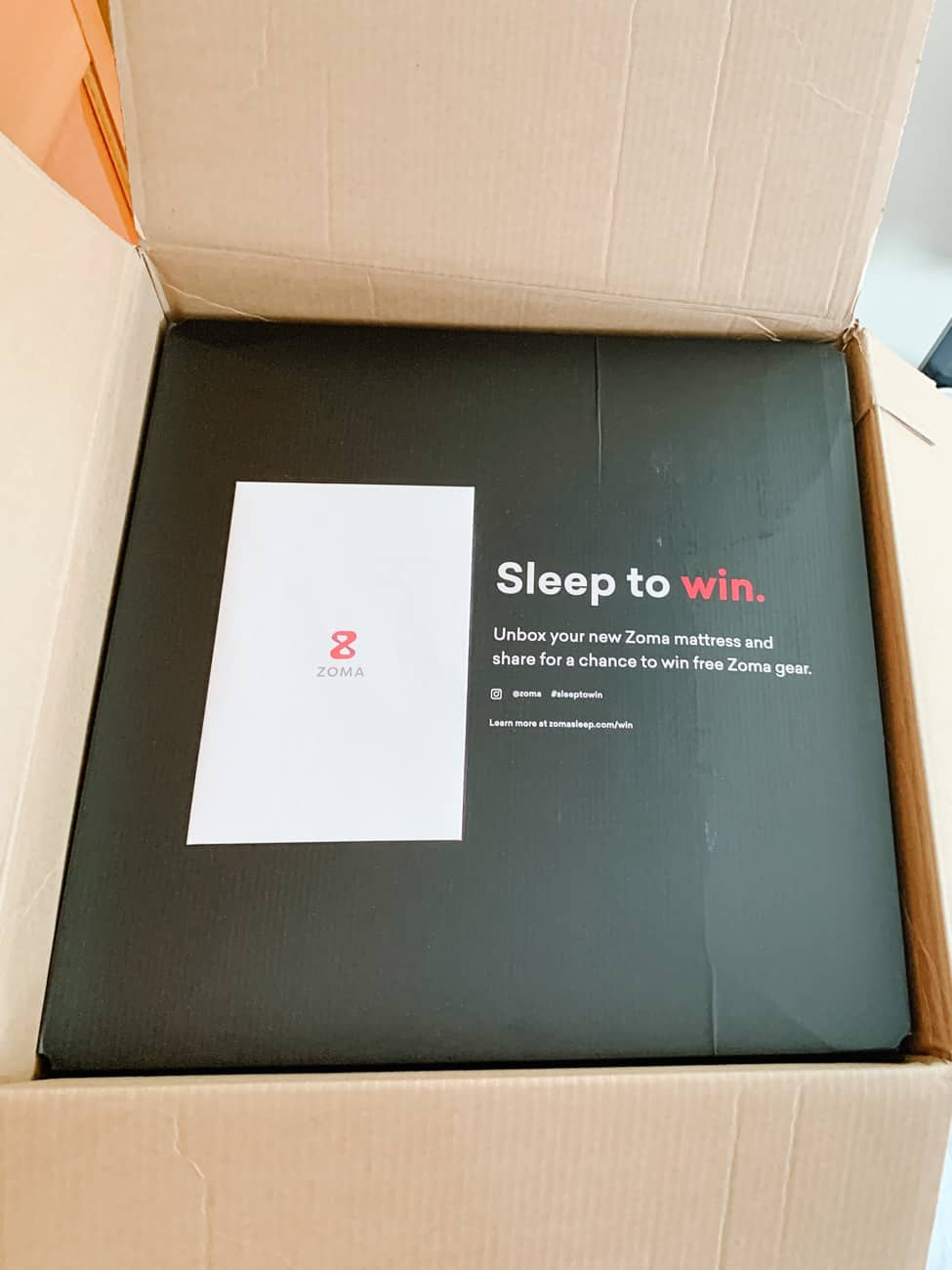 Top of the box from a Zoma mattress with text reading Sleep to Win