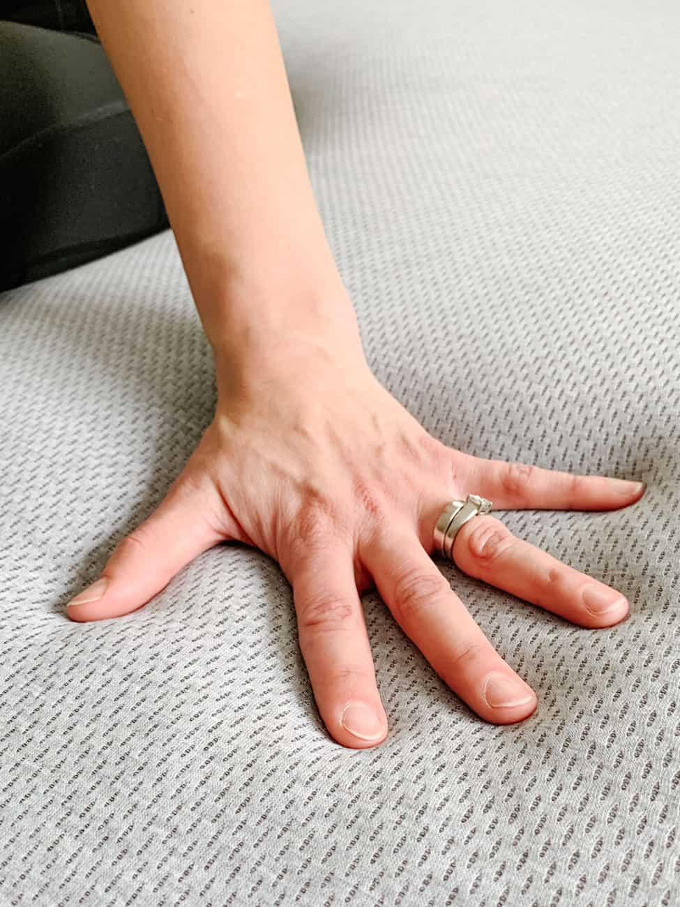woman's hand with rings pressed into a grey mattress