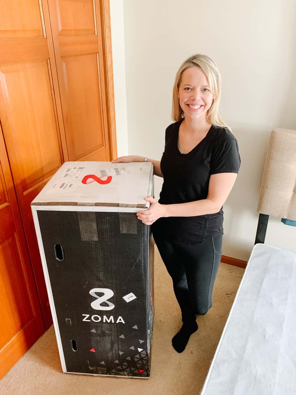 Zoma mattress bed in a box next to a smiling woman