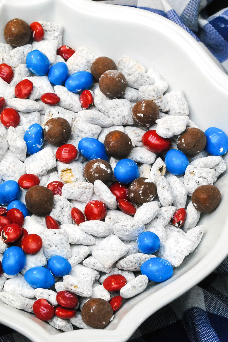 red, white and blue dessert snack mix with 4th of July candy and coated cereal in a white bowl over a blue and white napkin.