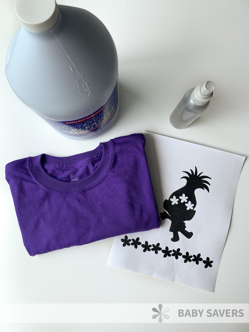 Bottle of bleach, spray bottle, purple t shirt and a printed silhouette of Poppy the troll