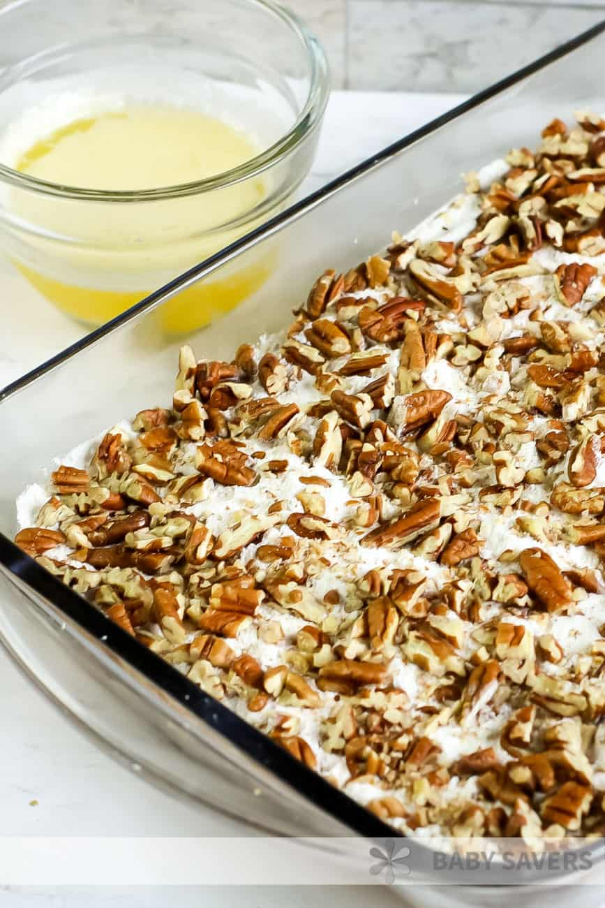 baking dish with unbaked pumpkin pecan crisp and a dish of melted butter on the side