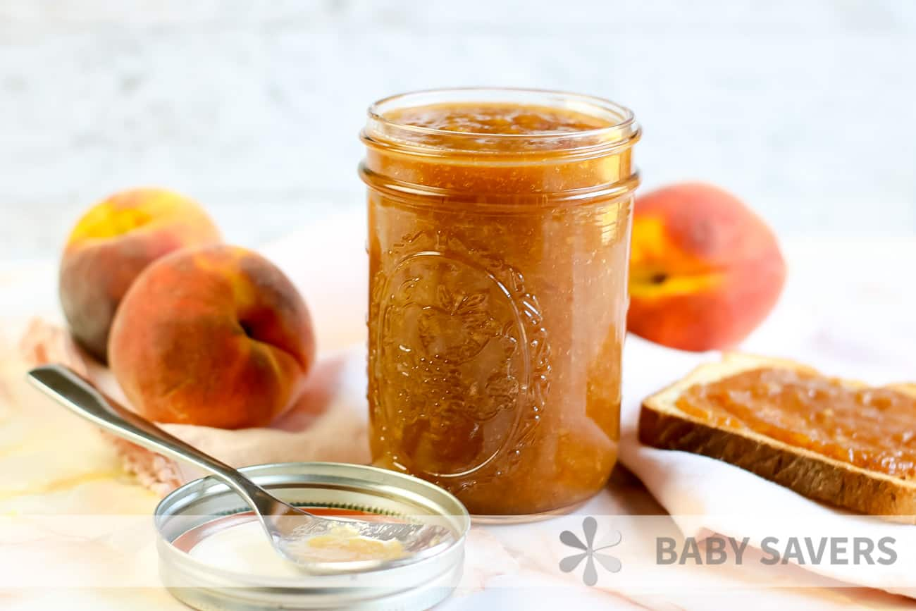 spoon with peach butter on it in front of a glass jar filled with peach preserves