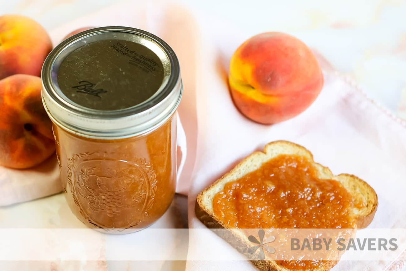 canned peach butter with a piece of toast and fresh peaches