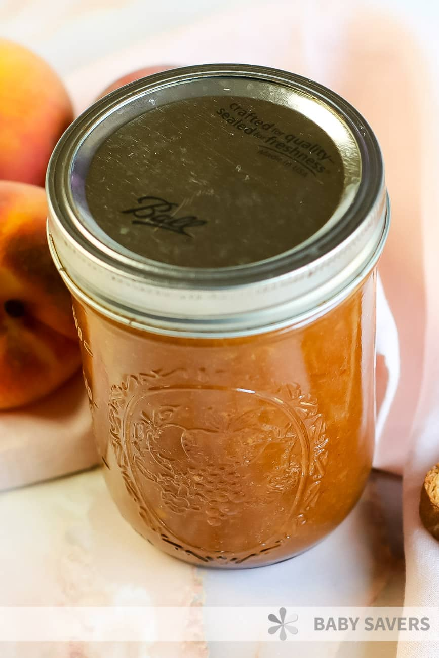 preserved and canned peach butter in a glass canning jar