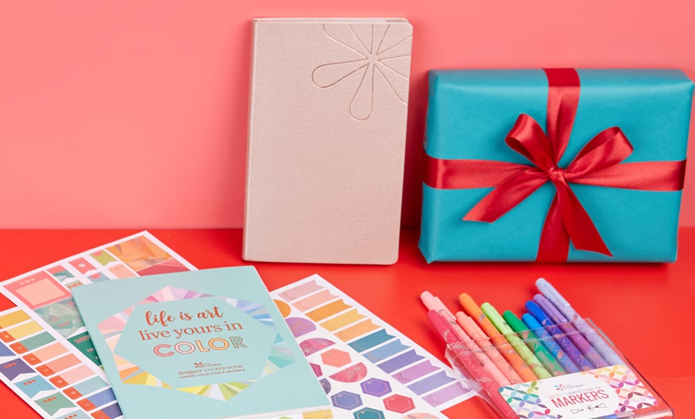 Erin condren stickers, pens, pouch and wrapped gift on a red and pink background