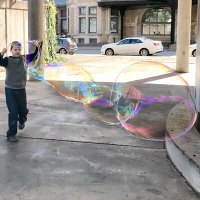 giant bubbles made by a boy with a string wand