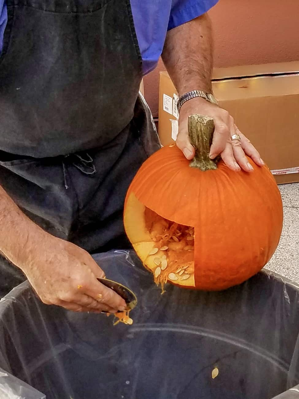 before using the Loki pumpkin stencil, man cleaning out seeds from a pumpkin